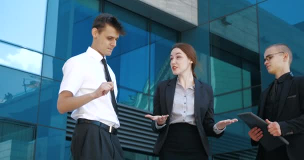 Close up three successful business people stand outdoors near blue glass wall, negotiate, debate, argue. Young confident woman explains to two men knowledge information, actively moves waving hands