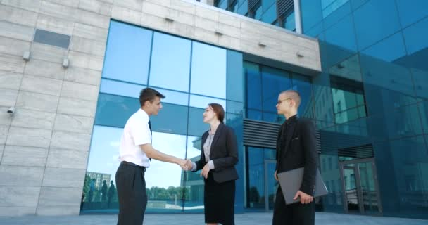 Three young employees standing near business center on break from work, talking actively joking laughing, concept of friendly colleagues. Two young men and woman in classic suits discuss news outdoor