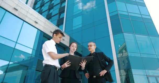 Group of partners young business people standing near building, discussing matters, solving problem, conducting brainstorming session. Three persons two men and woman communicate talking together