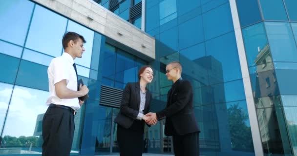 Drei Geschäftsleute stehen auf der Straße, einigen sich, kommen beim Treffen zu Kompromissen. Zwei Büroangestellte und zwei Büroangestellte schütteln sich die Hände, machen Abschiedsgeste, verabschieden sich, trennen sich, gehen in verschiedene Richtungen