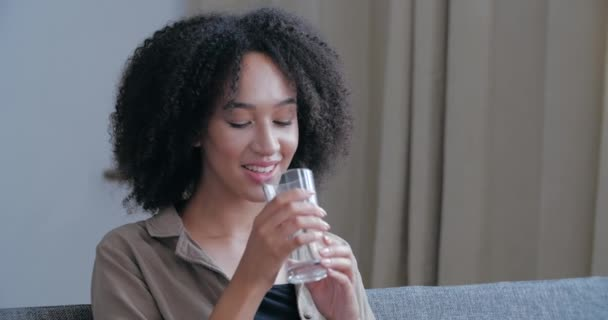 Smiling American young woman friendly looking at camera, holding glass of pure mineral cold water in her hands, taking care of health, feeling healthy, portrait close up