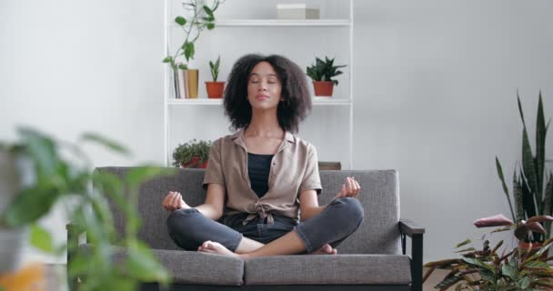 Calm relaxed African woman sitting at home on sofa with closed eyes, crossed legs, meditating, doing yoga asana practice. Mixed race girl practicing mindful deep breathing at home in room with plants