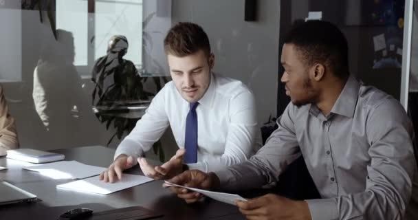 Sebevědomý běloch finanční poradce bankovní makléř vysvětlující dohodu výhody, mluvit o podnikání na soustředěný africký Američan muž, potřást rukou po dosažení dohody v kanceláři konference