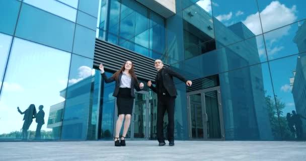 Ein Paar Kollegen, Frau und Mann in schwarzen Business-Anzügen, tanzen zusammen und bewegen ihre Arme und Beine auf der Straße unter freiem Himmel, zwei Geschäftsleute haben Spaß nach einem harten Tag, an dem sie den Sieg feiern