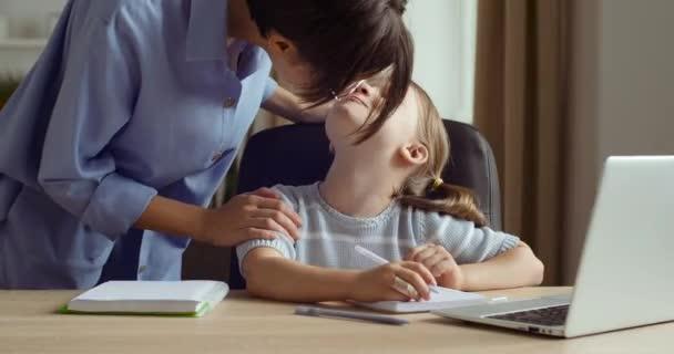 A lány otthon ül, távolról online tanul az e-tanulásról, laptopot néz, házi feladatot csinál, fiatal nő anya nővér vagy tanár áll gyermek csókokkal dörzsöli az orrát a lánya arcára