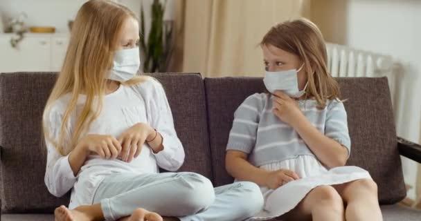 Zwei kleine Schwestern, blonde Freundinnen, die zu Hause auf bequemen Sofamöbeln sitzen und medizinische Schutzmasken auf den Gesichtern tragen und sich lachend anschauen, wie sie gemeinsam in Quarantäne Spaß haben.