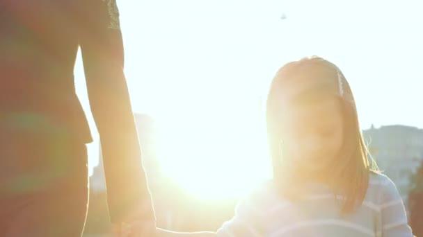 Közelkép boldog gyerekek arcát két lány naplemente fény szabadban. A női test részletei, az anya kézen fogva vezet pár lányt, bevásárlószatyrot cipel, a gyermek ránéz a csomagra, vidáman mosolyog.