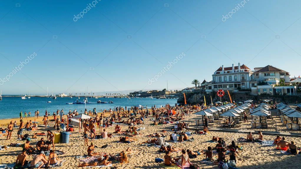Crowded sandy beach in Cascais near Lisbon, Portugal during the summer. This beach is known as Praia da Conceicao