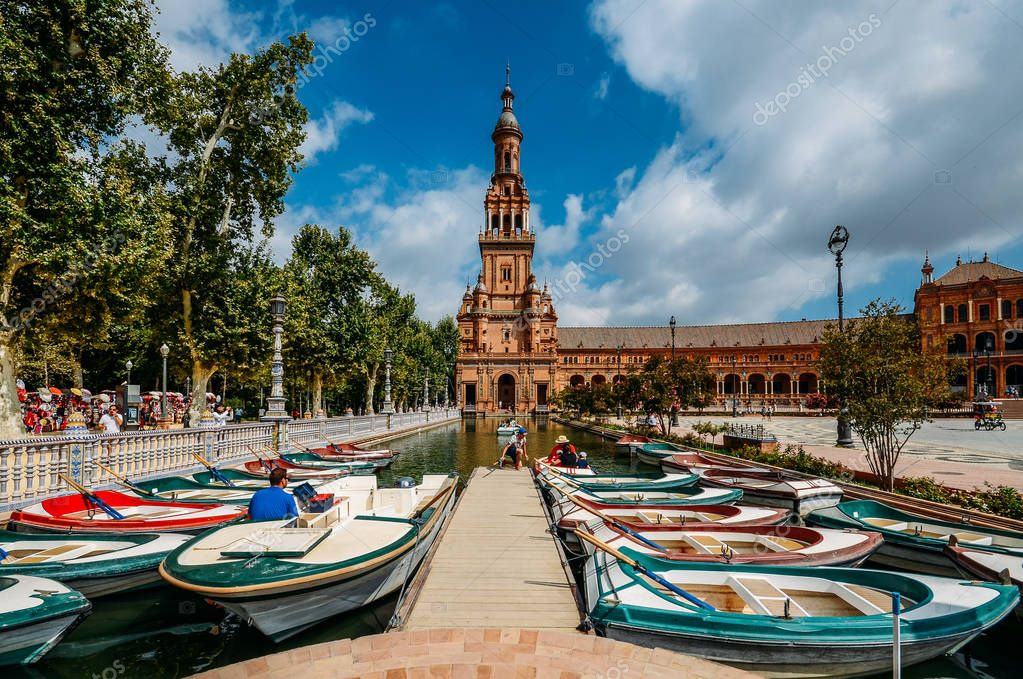 Boats and tourists on the canal in Spain Square or Plaza de Espana, Seville, Andalusia