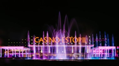 Facade of the Casino Estoril with colourful fountain show at night. Casino Estoril is one of the largest casinos in Europe and inspiration for Ian Flemings Casino Royale
