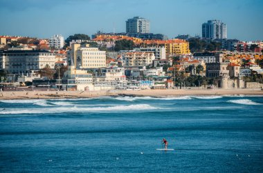 Man does stand up paddle overlooking the coast of Estoril near Lisbon, Portugal