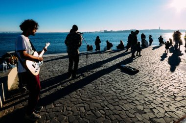 Street performers alongside the river Tagus on a sunny winter day