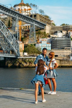 Young girl takesk a picture of couple at the Ribeira in the Douro River bank near the Dom Luis I Bridge, Porto, Portugal