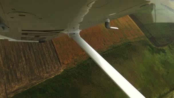 Let nad pole pohledu z kokpitu letadla. Letadlo se otáčí nad zemi