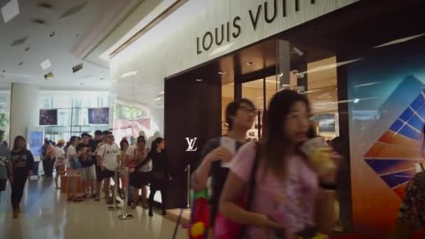 Unidentified people stand on the queue at Louis Vuitton Luxury boutique shop