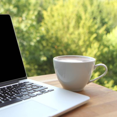 Mock up image of a pleasant morning using laptop with blank black desktop screen with a cup of coffee on a wooden table in an outdoor cafe