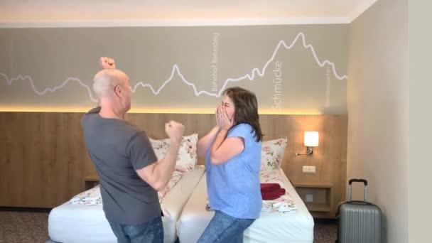 pozitivní pár, muž a žena středního věku v županech tančících v hotelovém pokoji, koncept dovolené, cestování, životní styl
