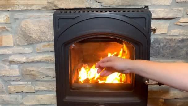 muž zahřívá zmrzlé ruce u jasně oranžového ohně v černém krbu, světlý plamen osvětluje místnost, útulný domácí koncept