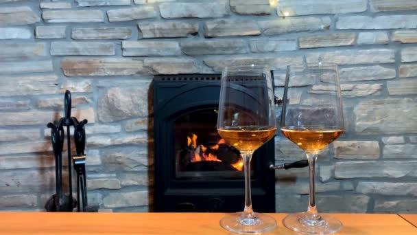 a kandalló előtti asztalon van két pohár bor, egy romantikus este koncepciója.