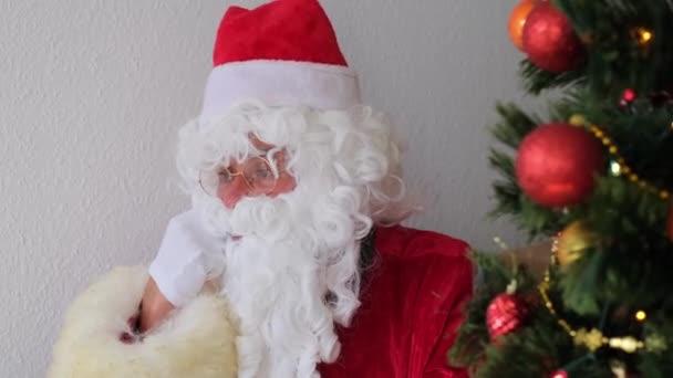 dospělý Santa Claus v červeném obleku sedí u stolu, vánoční stromeček je krásně zdoben míčky, věnce, koncept Vánoc, novoroční oslavy, dovolená prodeje a slevy, silvestr