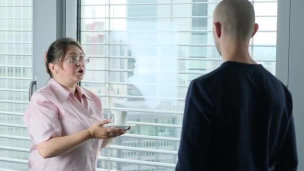 adult woman and young men stand in the office in front of the window, discuss, debate, concept of business idea, workplace, team spirit