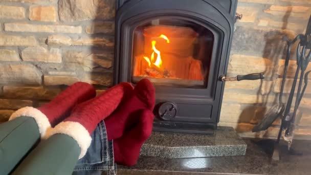 muž a žena leží u horkého hořícího krbu, nohy natažené v červených ponožkách k ohni, koncept Vánoc, zimní odpočinek