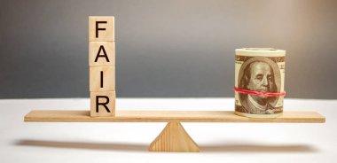 Dollars and the inscription Fair on wooden blocks. Balance. Fair value pricing, money debt. Fair deal. Reasonable price. Justified risk. Honest loan. Secured loans.