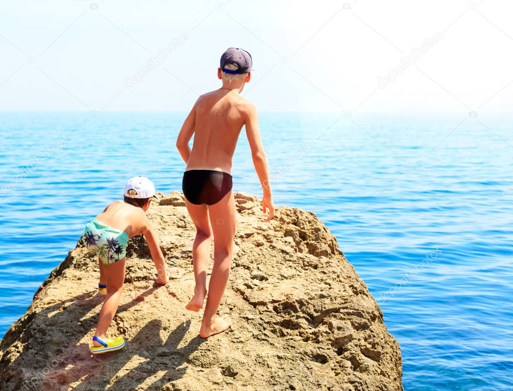 Two boys in swimming trunks climbing rocks on the stony beach