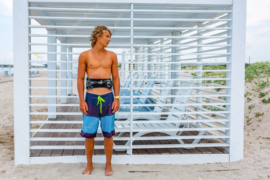 Young attceractive guy surfer stands on the beach looking out into the distance,