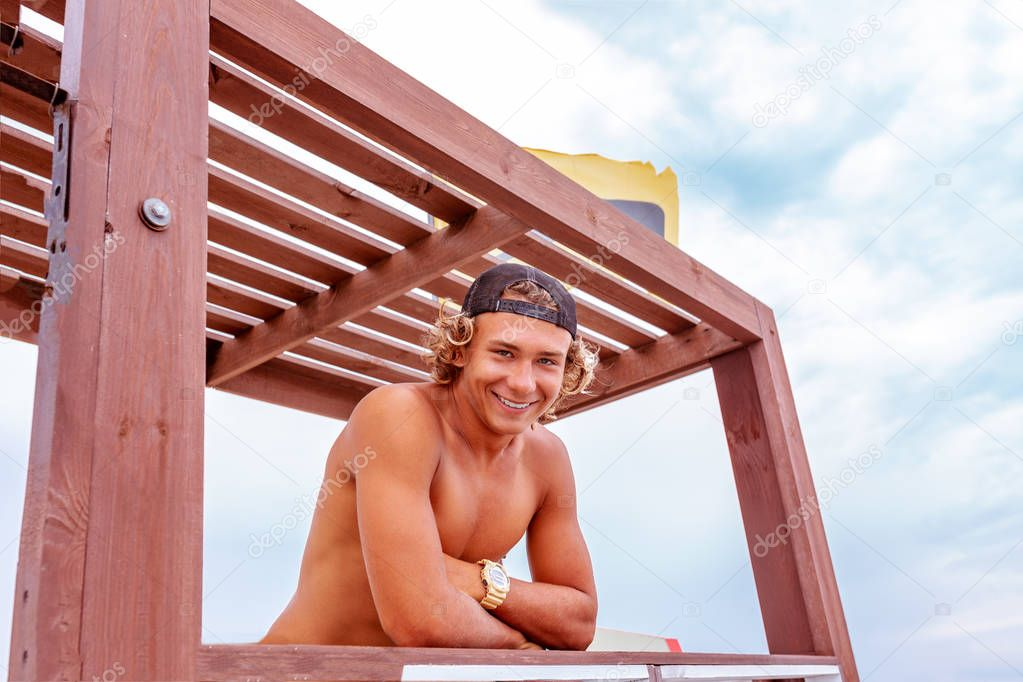 Young attceractive guy surfer standing on the terrace of a surf school looking at the camera