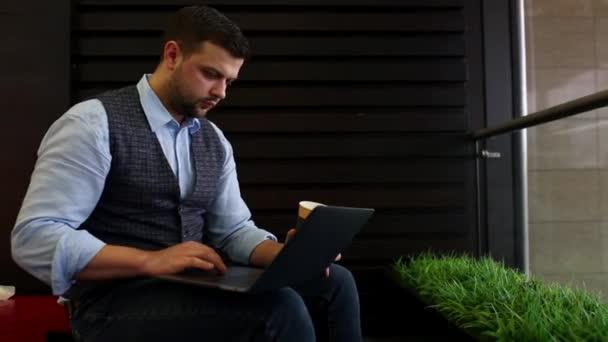 szabadúszó üzletember működő-ra laptop-diagramok használata a képernyőn a kávézó, és kávét iszik. Követés, és felfedi a lövés