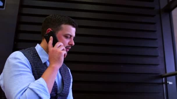 szabadúszó üzletember dolgozik laptop kávézó a képernyőn látható ábrák, ivó kávé és beszél a telefonon. Követés, és felfedi a lövés