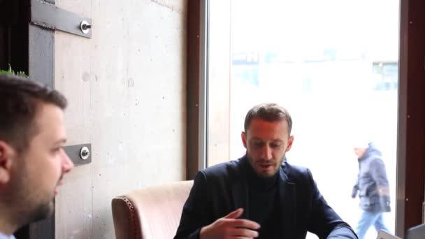 Dva podnikatelé u stolu café, pomocí přenosného počítače, pití čaje a mluví