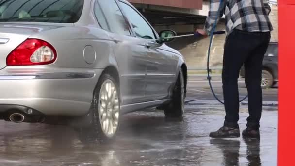 Man washing his car with water spray from high pressure washer  Car wash  self-service