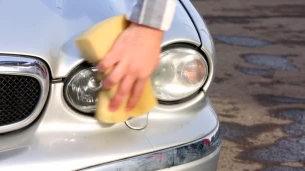 muž pečlivě umýt jeho oblíbené auto s houbou. Samoobslužné mytí aut
