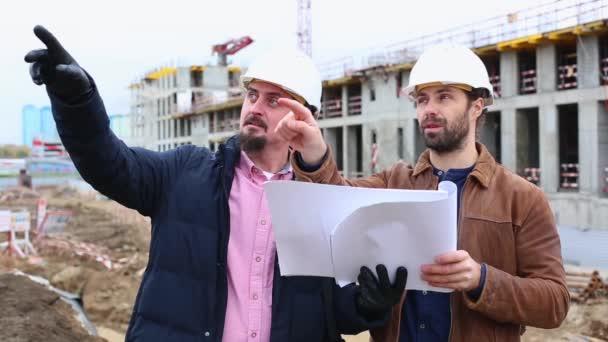 Dva technici hovoří o projektu pro stavební konstrukce. Dívají se na oba projekty papíru