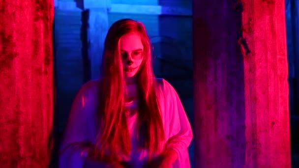 Frau mit toten Braut Make-up für Halloween stehen mit dem Auto in die weiße Brautkleid im Dunkeln bei verlassenen Haus