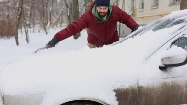 Man cleaning snow from car with brush in living house district