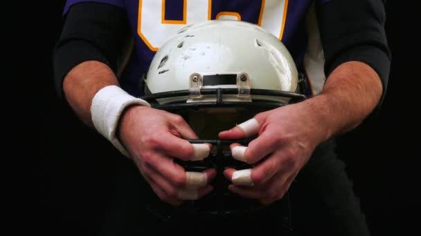 Amerikai futball. Amerikai-futball játékos tartja a sisak, mindkét kezével. A nagy amerikai labdarúgó játékos. Felkészülés a játék. A képzés. Közelkép, fekete háttér