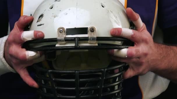 Amerikai futball. Amerikai futball játékos sisak mindkét kezével. Kezei sisak közelről. Amerikai-futball játékos kezében egy sisak bontakozik ki a képernyőn. Felkészülés