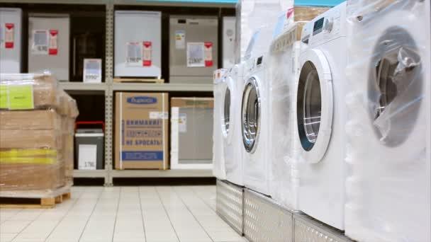 junger Mann, der in einem großen Geschäft Kleidung aus der Waschmaschine holt. Comic-Video