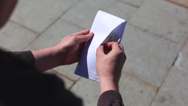 Close up of cash in envelope in hands. Money bonus in a paper envelope. A man holding an envelope with money. World bribe. The concept of fraud and corruption. Credit company financial services