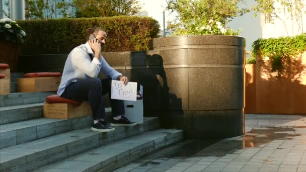 Unemployment, unemployed person, dismissal, downsizing. A man without a job. A young man sits on the street with a sign fired, need a job.