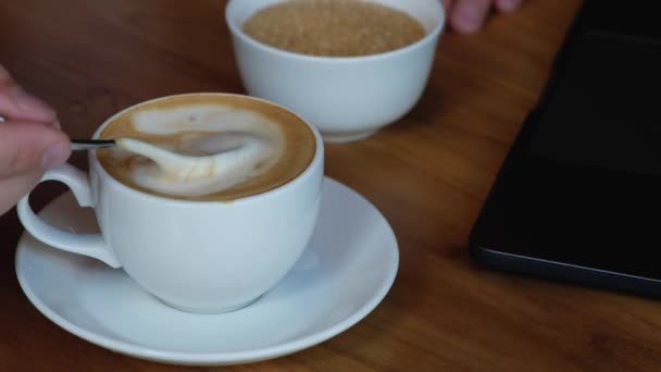 man stirs sugar in a cup with coffee. on the table next to a laptop.