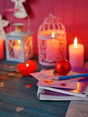 Gül, mumlar, yanan ile dekoratif fener şeklinde mumlar yanan dekoratif kompozisyon Sevgililer günü kalpleri, defter ve kalemler, Festival dekor dokusal ahşap bir masa mor, pembe renkli romantik bir iç üzerinde kırmızı keçe