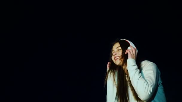 Dospívající se sluchátky si zatančíte hudební beat Zpomalený pohyb na černém pozadí. Šťastná dívka poslouchat oblíbenou hudbu pomocí přehrávače smartphone a sám se těší mimo krásné 20s