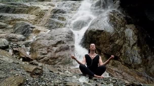 Woman practicing yoga at waterfall with headphones