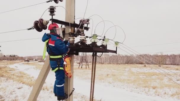 Riparatore che lavora alla linea elettrica con fili di tensione in stazione