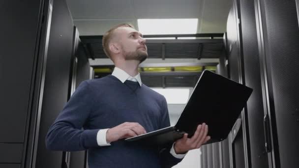 Mann hält Laptop und diagnostiziert Rechenzentrum im Serverraum