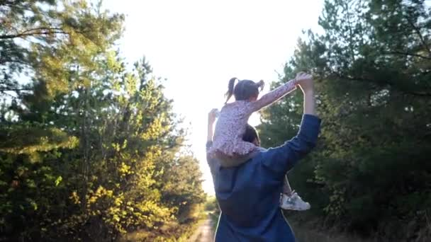 Active mom rolling little happy daughter on neck, family plays fun game together